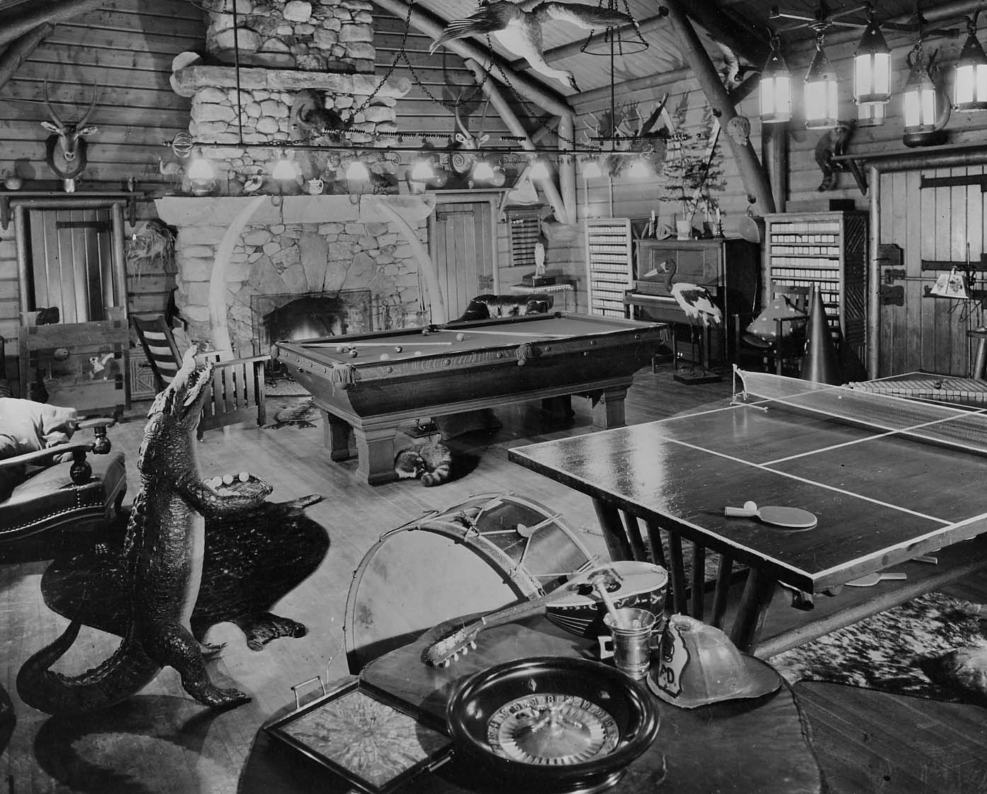Adirondack Museum Collection. Photo description: Scene of game room at Great Camp Sagamore. Pool and ping-pong tables at center of room, various musical instruments around. Large fireplace at back of room. Mounted animals and birds throughout the room. Stuffed Aligator holding ping-pong balls at left, sleeping raccoon under pool table. Mounted to board with P6892 on reverse.