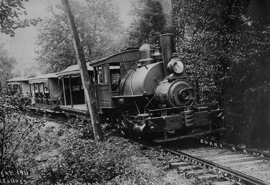Adirondack Museum Collection. Photo description: Marion River Carry Train, 1911,;Rassie Scarrit at the throttle. 1911 - Kellogg, E.E. photo