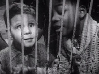 Stills from one of the movie reels found within the metal suitcase shows what appears to be two blind children in a cage-type environment (indianlakeproject.blogspot.com image).