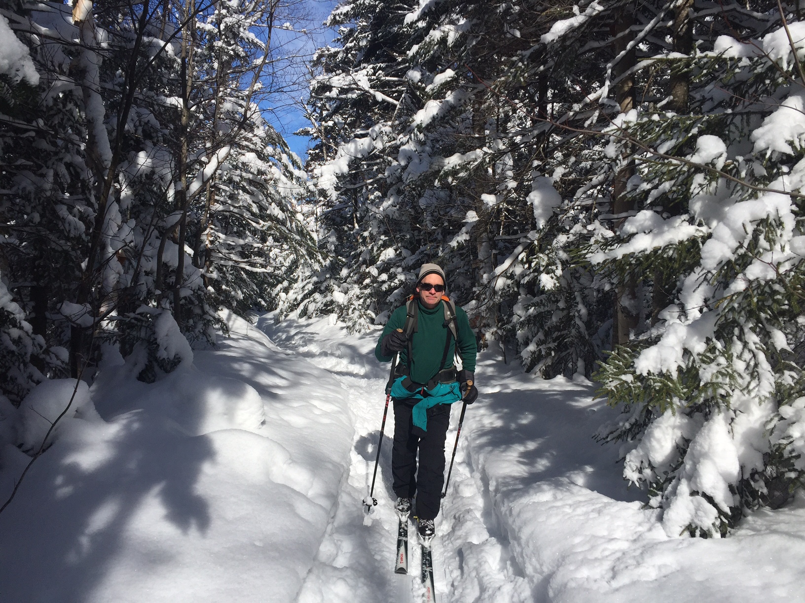 Cross country skier on wooded trail with heavy snow