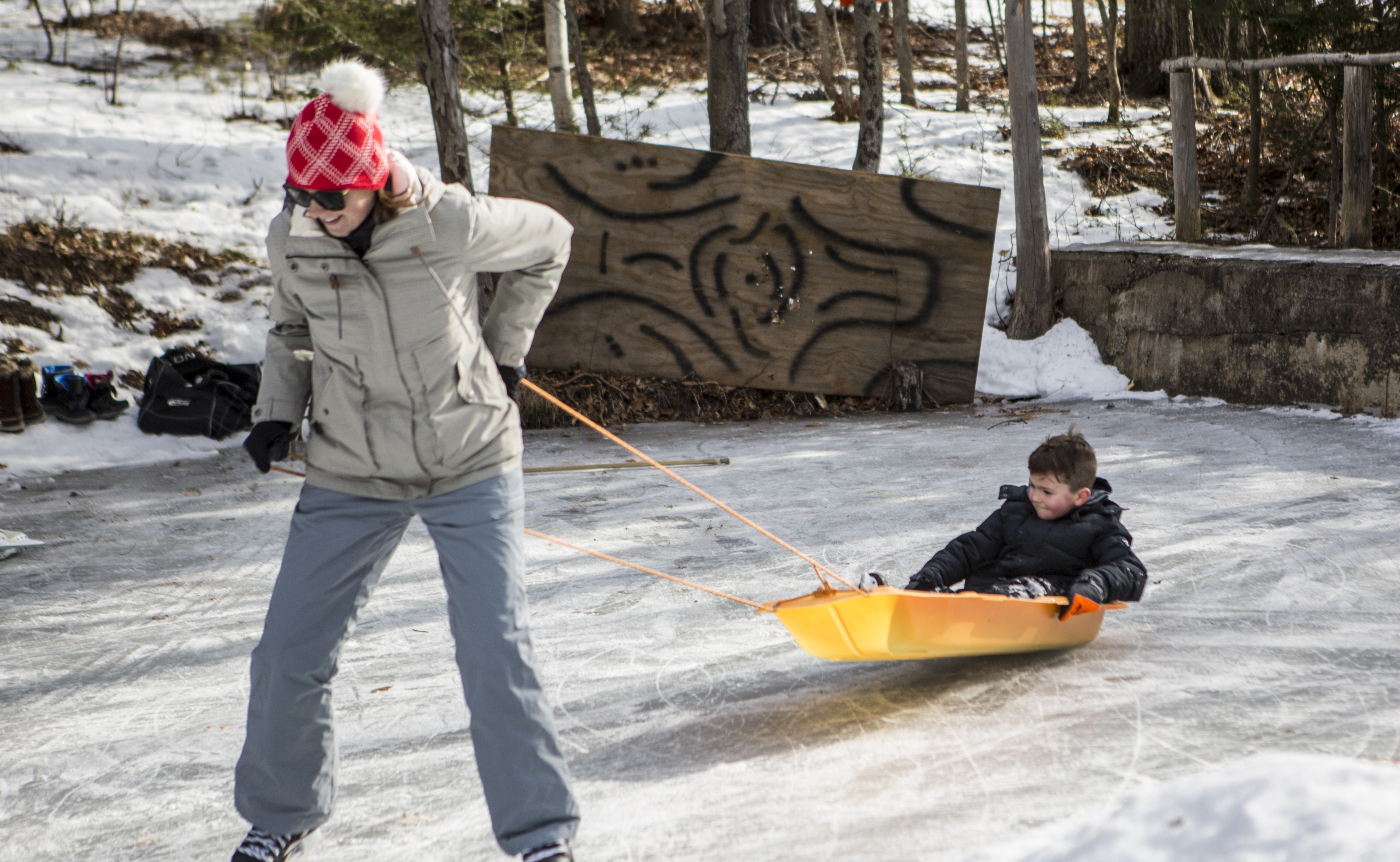 Woman skating on a pond and pulling kids in a sled