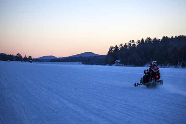 Snowmobiling in Long Lake at sunset.