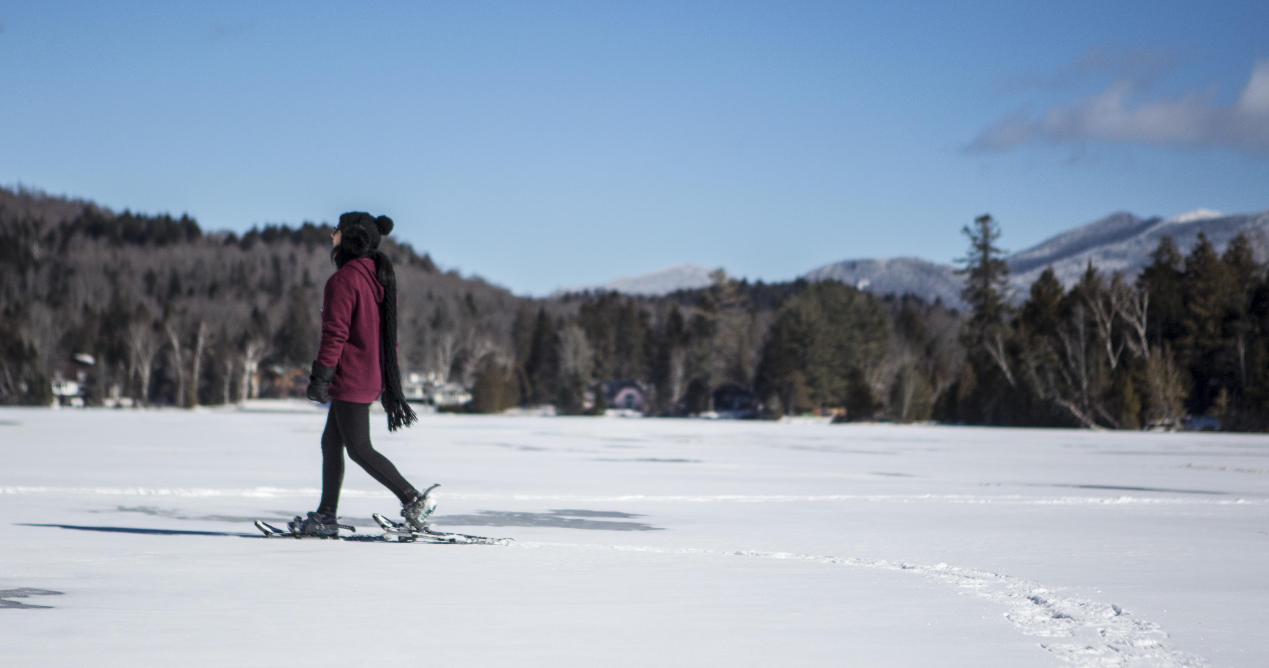 Woman snowshoeing on lake